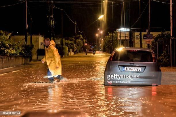 A man walks through flood waters across a road near Corinth during a rain storm on September 29 2018