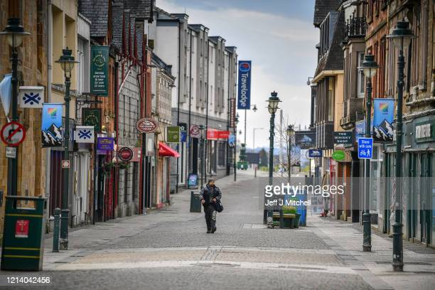Man walks through Fort William Main Street as people have been asked to stop traveling to the Scottish Highlands in a bid to avoid spreading the...