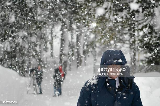 A man walks through heavy snow fall towards the Congress Centre in the resort town of Davos ahead of the World Economic Forum 2018 annual meeting on...