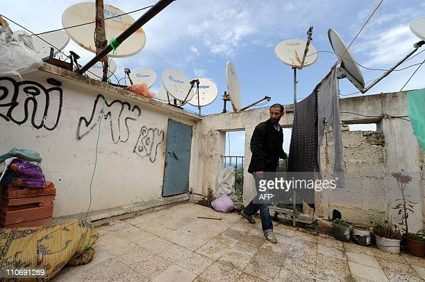 A man walks through illegal housing built atop a preexisting residential buidling in the 'Climat de France' neighborhood in Algiers on March 23 2011...