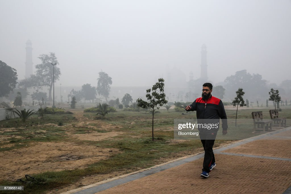 A man walks through Iqbal Park shrouded in smog in Lahore Pakistan on Tuesday Nov 14 2017 The fates of 15 billion people in both India and Pakistan...