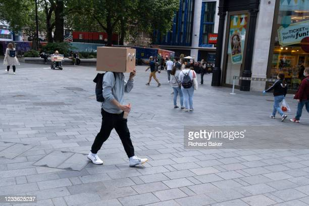 Man walks through Leicester Square with a cardboard box on his head, on 23rd June 2021, in Westminster, London, England.