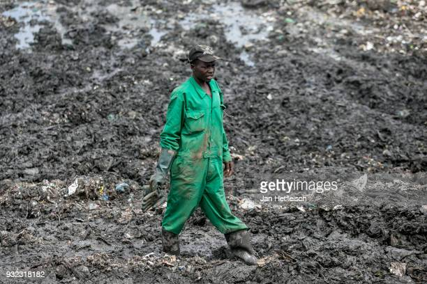 A man walks through mud at the Dandora rubbish dump on March 14 2018 in Nairobi Kenya The Dandora landfield is located 8 Kilometer east of the city...