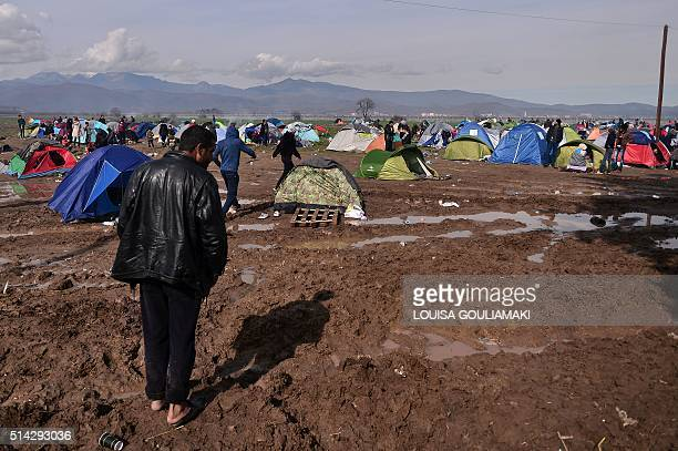 A man walks through mud at the makeshift camp at the Greek Macedonian borders near the village of Idomeni on March 8 where thousands of refugees and...