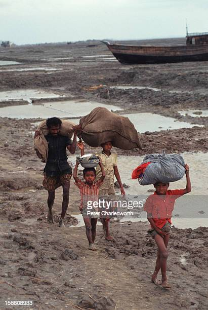 A man walks through muddy fields with his children with all their worldly possessions on their heads after surviving one of the biggest cyclones to...