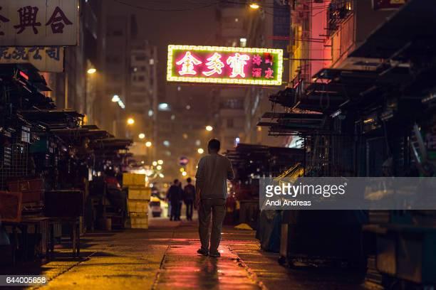 Man Walks Through Neon colored street in Hong Kong