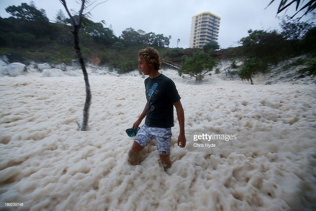A man walks through ocean foam in Snapper Rocks as Queensland experiences severe rains and flooding from Tropical Cyclone Oswald on January 28, 2013 in Gold Coast, Australia. Hundreds have been evacuated from the towns of Gladstone and Bunderberg while the rest of Queensland braces for more flooding.