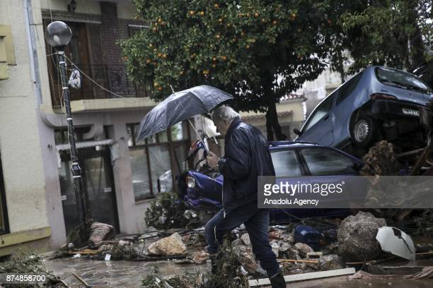 A man walks through puddles after torrential rains struck the west Athenian suburb of Mandra Greece on November 16 2017 At least nine people have...