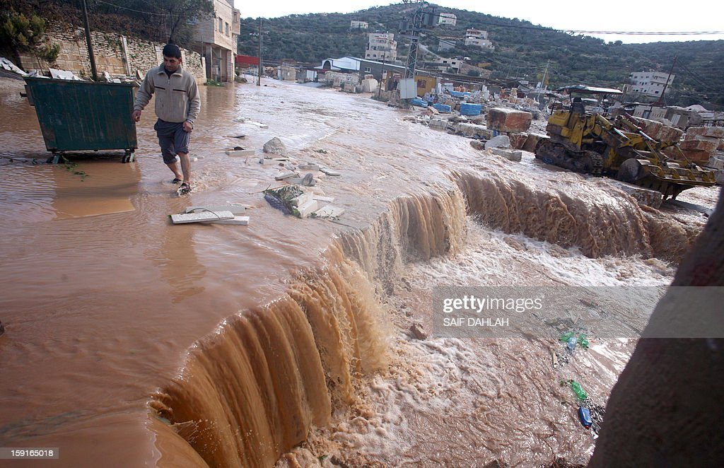 A man walks through rain water in the village of Qabatiya, in the Israeli occupied West Bank near the northern city of Jenin, on January 9, 2013, as rain storms and snow engulfs the Levant.