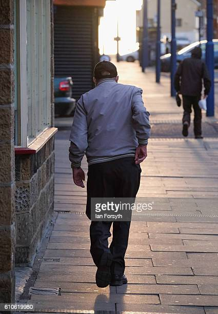 A man walks through Redcar high street on September 27 2016 in Redcar United Kingdom One year on since the SSI steel making plant at Redcar was...