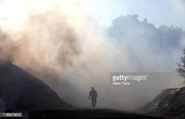 A man walks through smoke during a flare up at a mulch supplier during the Saddleridge Fire on October 12 2019 in Sylmar California The winddriven...