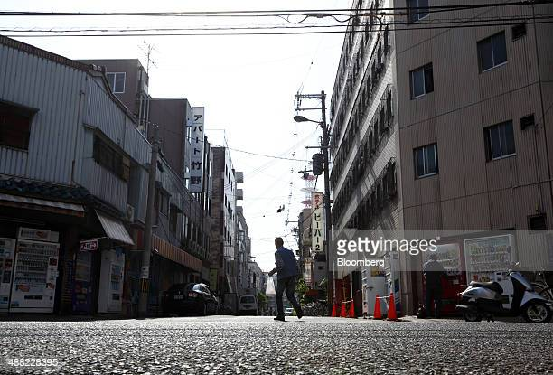 A man walks through the Airin area of Nishinari ward in Osaka Japan on Friday May 2 2014 Osaka prefecture's economic output dropped 62 percent to 366...