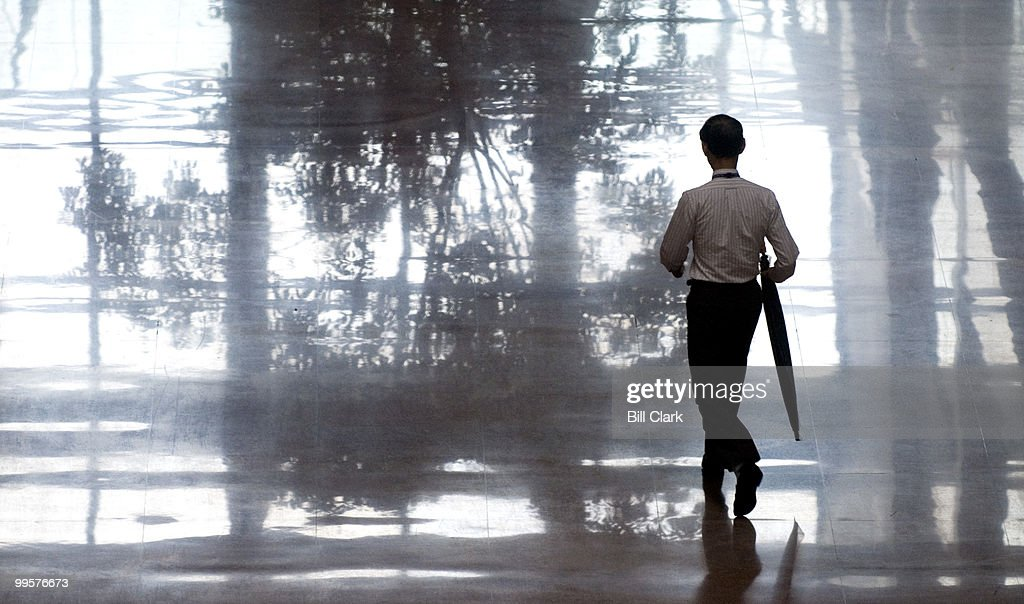 A man walks through the atrium of the Hart Senate Office Building on his way outside during a rainy and windy Friday Oct. 6, 2006.