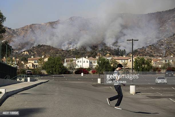 A man walks through the Azusa Pacific University parking lot as wildfires burn in foothills on January 16 2014 in Azusa California Authorities have...