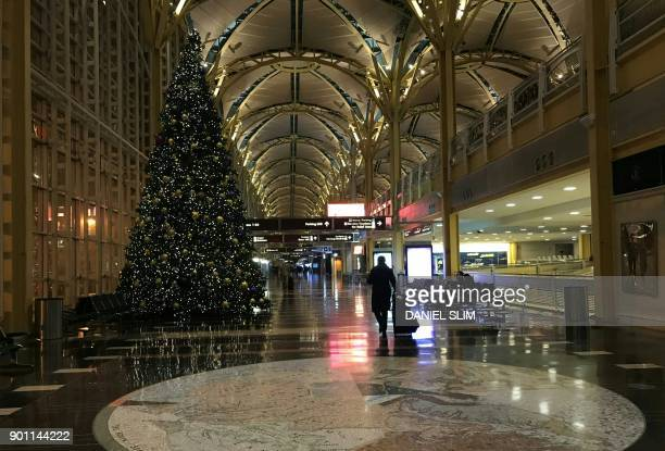 A man walks through the empty lobby of Ronald Reagan airport near Washington DC early January 4 2018 as winter storm Grayson sets in on the East...
