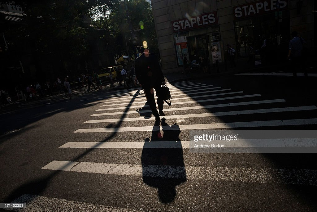A man walks through the Financial District, only a few blocks from the Ground Zero construction zone, on June 24, 2013 in New York City. Construction began on One World Trade Center, the primary building of the new site, on April 27, 2006 and the final piece of the tower was installed on May 10, 2013, making it the tallest building in the Western Hemisphere. Construction is still ongoing on the surrounding complex.