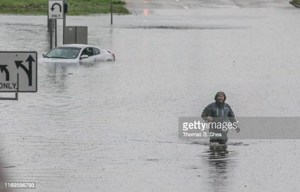 A man walks through the flooded feeder roads off of highway 69 North on September 19 2019 in Houston Texas Gov Greg Abbott has declared much of...