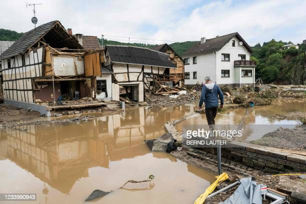 Man walks through the floods towards destroyed houses in Schuld near Bad Neuenahr, western Germany, on July 15, 2021. - Heavy rains and floods...