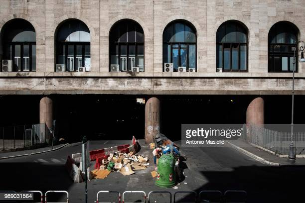 A man walks through the garbage in the neighborhood of Termini train station central Rome during summer time on July 01 2018 in Rome Italy