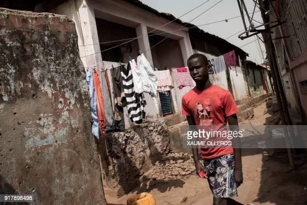 A man walks through the Mindara neighbourhood in Bissau on Mardi Gras on February 13 2018 / AFP PHOTO / Xaume Olleros