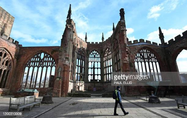 A man walks through the ruins of the 14th century Gothic Coventry Cathedral in Coventry central England on February 12 2020 which was bombed by the...