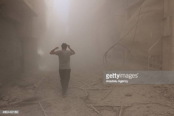 A man walks through the smoke after an airstrike staged by Syrian regime forces to the opposition residential areas in Duma district in the Eastern...