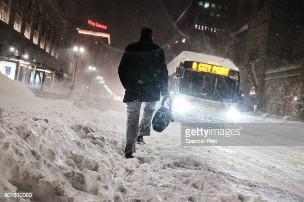 A man walks through the streets of Boston as snow falls from a massive winter storm on January 4 2018 in Boston United States Schools and businesses...