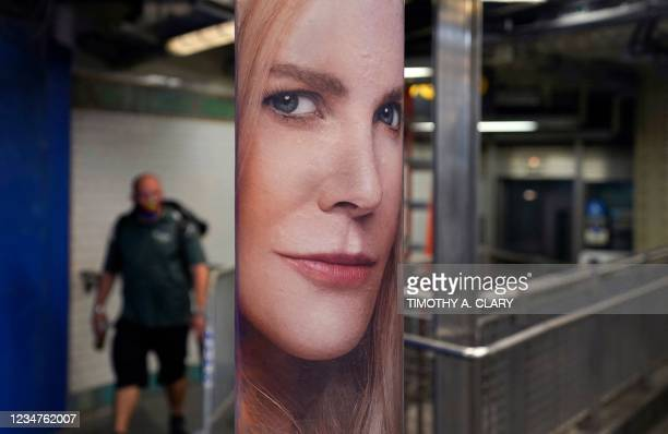 """Man walks through the subway in New York next to a poster of actress Nicole Kidman on August 19 to promote the mystery thriller, """"Nine Perfect..."""