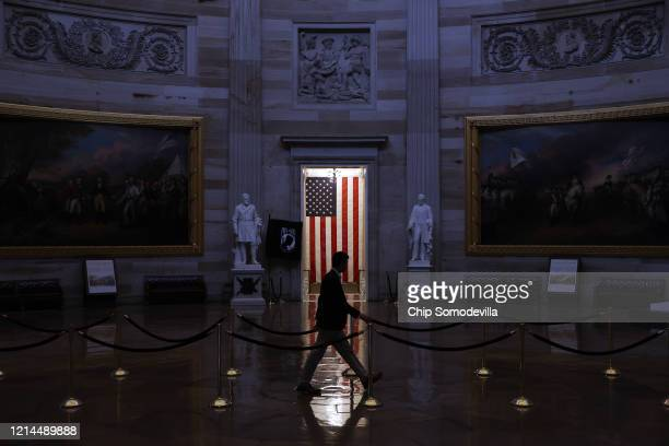 Man walks through the U.S. Capitol Rotunda, empty of tourists as only essential staff and journalists are allowed to work during the coronavirus...