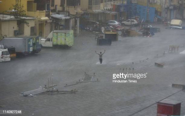 A man walks through the waterlogged street as cyclone Fani hits the coast on May 3 2019 in Puri India Cyclone Fani on Friday lashed Odisha triggering...