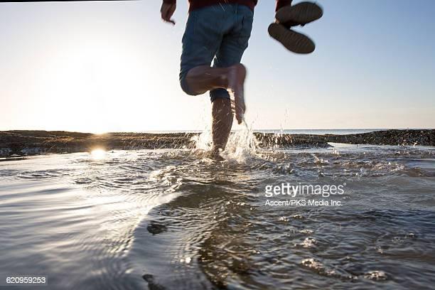 Man walks through tidal pool at sunrise