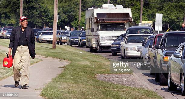 A man walks to a gas station that is givng out free gas during a promotion at a gas staion June 14 2007 Warren Michigan Hundreds of motorists lined...