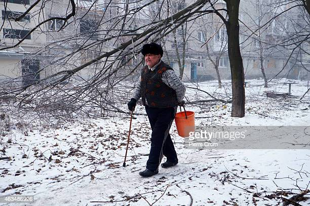 A man walks to collect water from a shelled pipe in the morning of the ceasefire on February 15 2015 in Donetsk Ukraine The Nothern suburbs of...