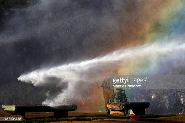 Man walks to the splash of water fird by a water cannon during the protest against government of President Sebastian Piñera on December 09, 2019 in...