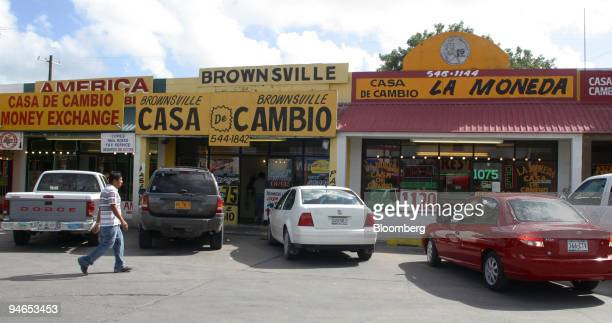 A man walks toward some Casa de Cambio money exchange businesses in a strip mall in Brownsville Texas just blocks away from the border crossing into...