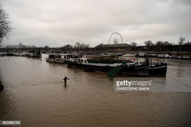 TOPSHOT A man walks towards a barge in the water of the river Seine after it burst its banks near the Grand Palais and the Grande Roue in Paris on...