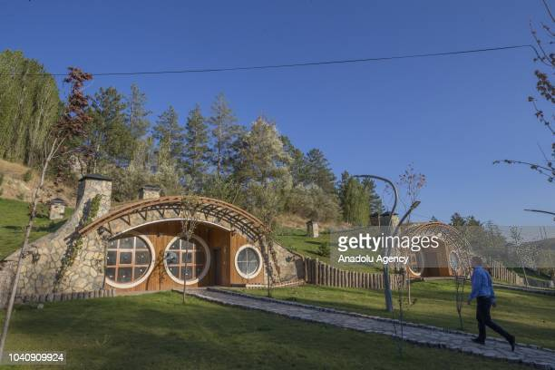 "Man walks towards a house, built with the inspiration from Hobbit houses in the movie ""Lord Of The Rings"", at Pasabahce Mesire area in Sivas, Turkey..."