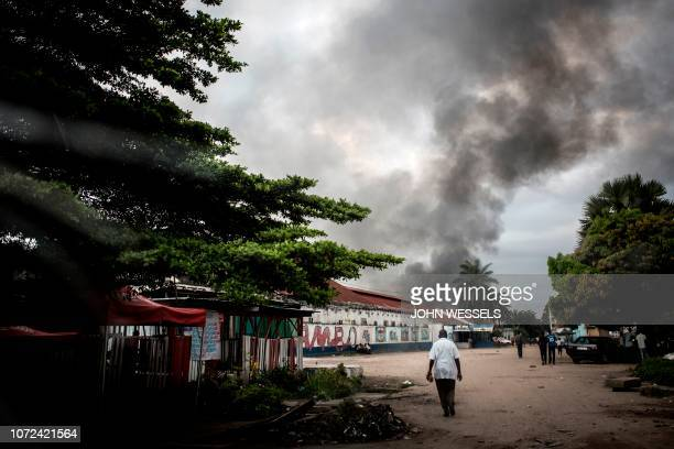 A man walks towards smoke rising from a fire at the independent national electoral commission's warehouse on December 13 2018 in Kinshasa ten days...