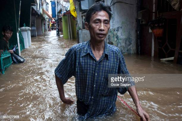 Man walks trough flooded water at Kampung pulo sub-district on January 13, 2014 in Jakarta, Indonesia. Over 5000 people have been evacuated from...