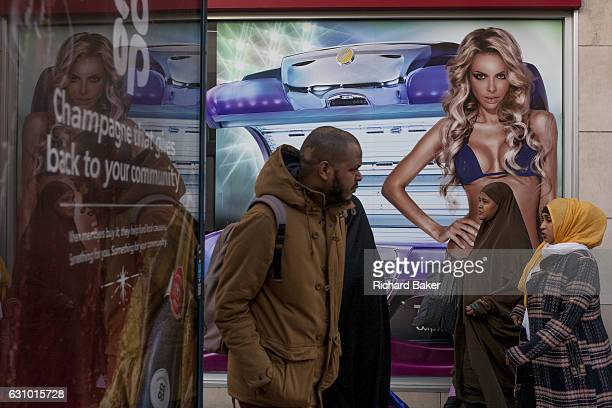 A man walks two Muslim women and an image of a girl wearing a bikini in a highstreet advert for sunbeds on 26th December 2016 in Bristol's Broadmead...