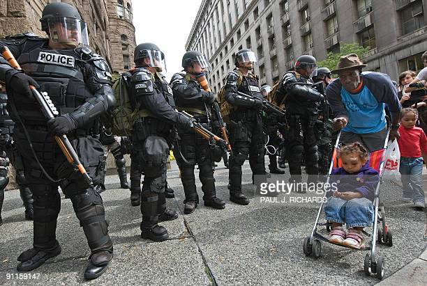 A man walks two young girls as police in riot gear guard the streets during protests in Pittsburgh Pennsylvania as world leaders attend the G20...