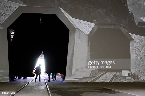 A man walks under a curtain next to a projection of the North entrance of the new Gotthard Base Tunnel prior to the ceremonial opening on June 1 2016...