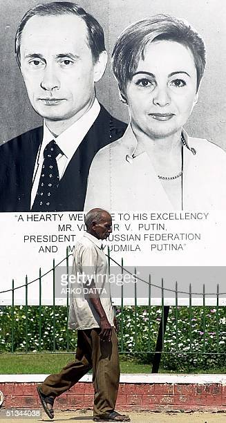 Man walks under a larger portrait of Russian President Vladimir Putin and his wife in New Delhi street 02 October 2000 welcoming the visiting couple....