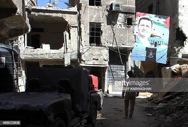 A man walks under a portrait of Syrian President Bashar alAssad in a street inside the Yarmuk Palestinian refugee camp in the Syrian capital Damascus...