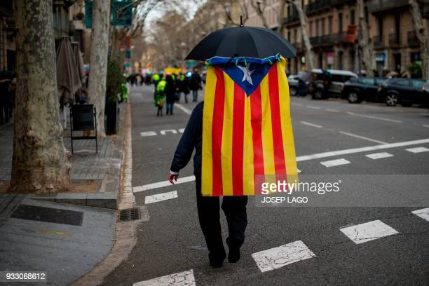 A man walks under an umbrella holding a Catalan proindependence 'Estelada' flag during a demonstration titled 'The democratic and cohesive school is...