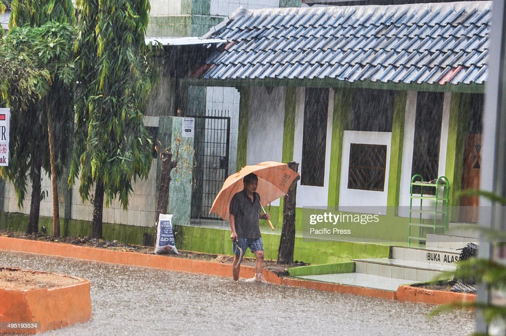 A man walks under an umbrella through the rain in Kapasa. : News Photo