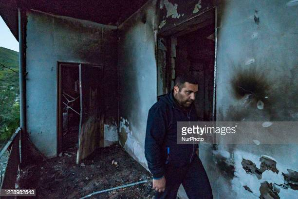 Man walks under his destroyed house by an azeri rocket during the combats between Nagorno Karabakh and Azerbaijan armies on October 9, 2020.