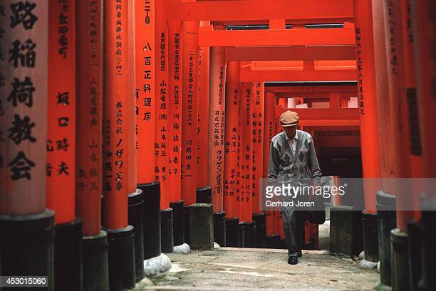 A man walks under the tori at Fushimiinari Shrine Founded in the year 711 this shrine has four kilometers of trails covered by an enormous number of...
