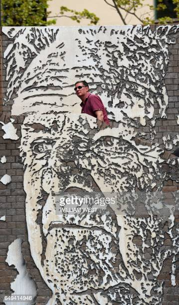 Man walks up a staircase adorned with a mural by artist Alexandre Farto of Jack Mundey in the Rocks district of Sydney on March 2017. Mundey was a...