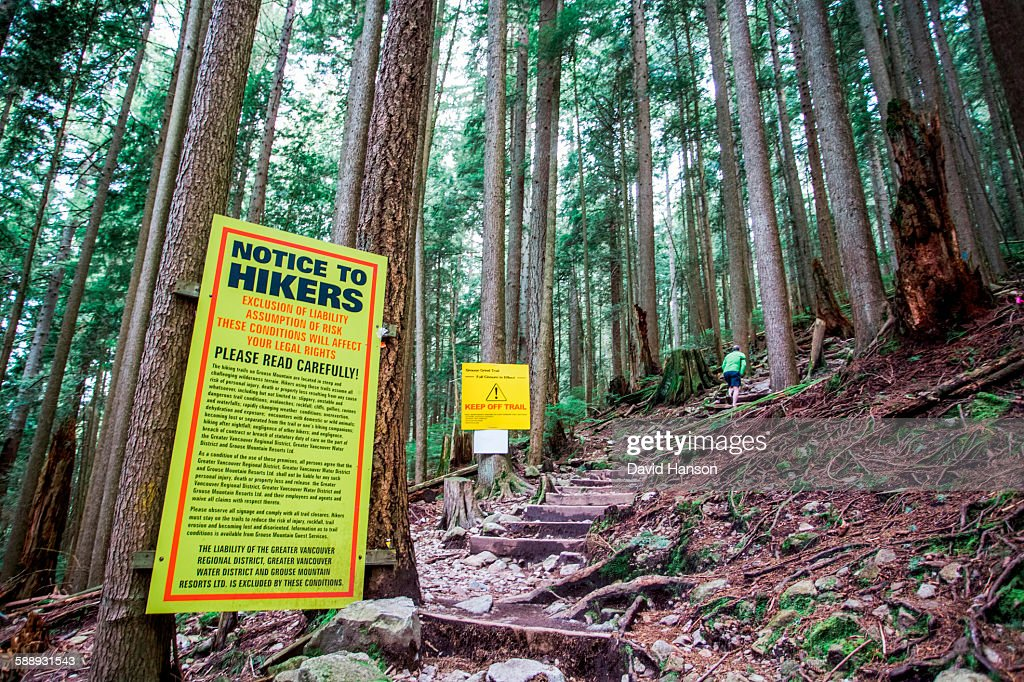 VANCOUVER, BRITISH COLUMBIA, CANADA. A man walks up a steep trail past a giant yellow sign full of legal disclaimers and Keep Off Trail warnings. : Stock Photo